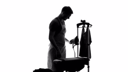 гладильный : Smiling male householder ironing clothes on board, sharing of housework duties