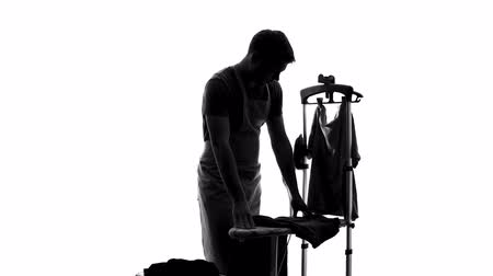 гладильный : Husband silhouette in apron feeling tired of ironing clothes, housework routine