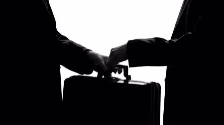 átadó : Two men handshaking after transferring suitcase, business agreement, bribe