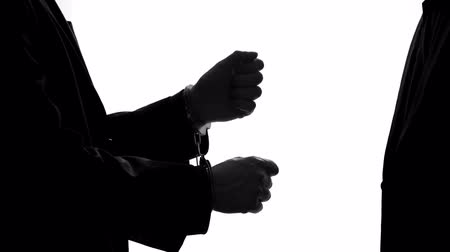 manşet : Criminal businessman giving bribe and releasing prison, taking handcuffs off Stok Video
