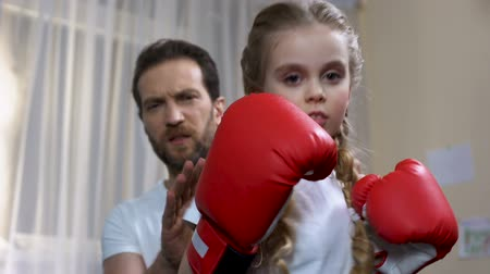 schoolkid : Boxing school girl practicing punches with father at home, self-defense lesson Stock Footage