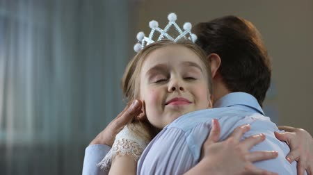 príncipe : Cute little girl in princess crown dress hugging father, tender relations, party Stock Footage