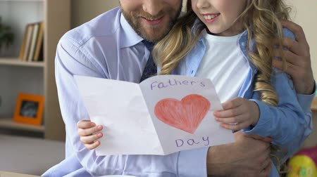 otcovství : Happy man hugging daughter holding handmade fathers day card, tender relations Dostupné videozáznamy