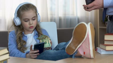 ignore : Girl in headphones taking father money and putting pocket, spoiled child, ignore Stock Footage