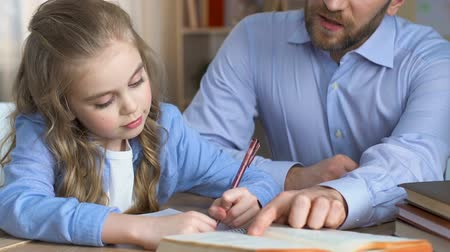 tables : School girl doing homework with teacher, additional education, child development