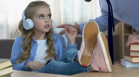 scold : Strict father shouting at daughter listening to music in headphones in room