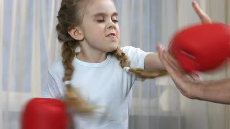 esportivo : Girl practicing boxing punches with father at home, sport education.