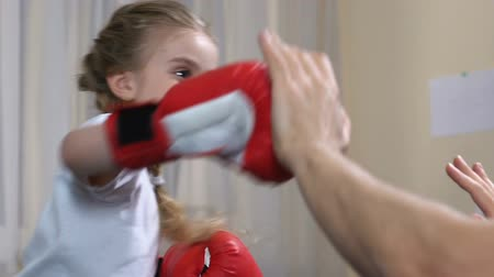 defesa : Small girl boxing father and showing success gesture, sport child development