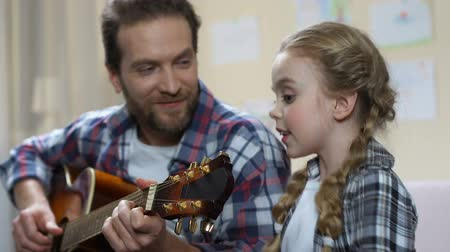 śpiew : Daughter singing father playing guitar, school performance rehearsal, having fun