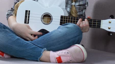 acoustical : Girl learning to play ukulele, musical hobby, children creativity, free time