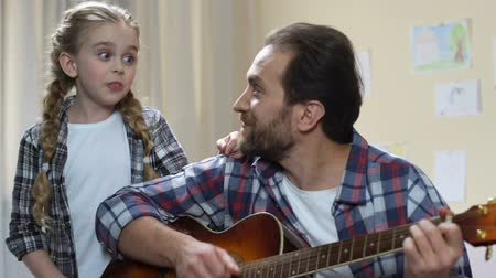 śpiew : Talented daughter singing while father playing guitar, musical hobby.