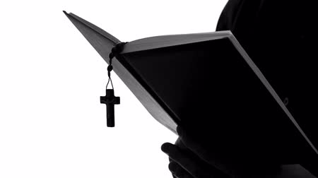 persuasion : Priest silhouette reading Bible, celebrating Mass, religious sect, close up