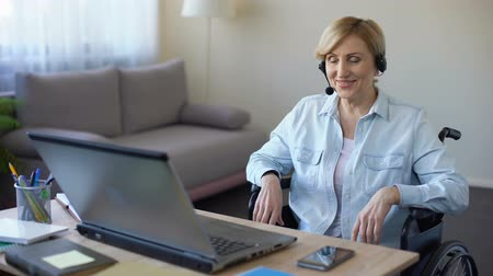 paraplegic : Senior businesswoman in wheelchair working on laptop, video conference online