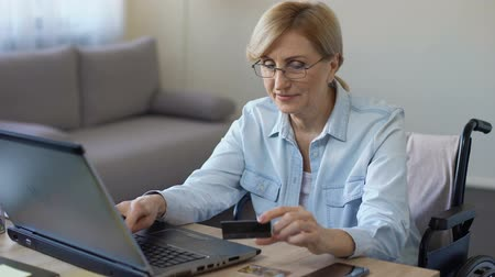 clientes : Happy adult woman in wheelchair entering card number on laptop, shopping online