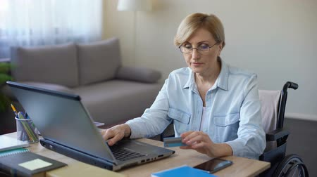 inwalida : Nice senior woman in wheelchair typing card number on laptop, paying bills
