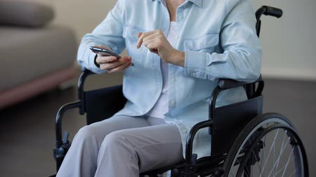 sedmdesátá léta : Female pensioner in wheelchair browsing internet on smartphone, communication Dostupné videozáznamy