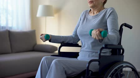 штанга : Senior woman in wheelchair lifting dumbbells, doing exercises at home, recovery Стоковые видеозаписи