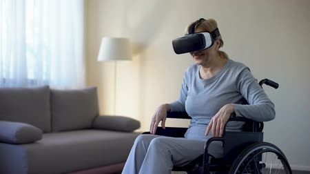 sedmdesátá léta : Retired woman in wheelchair wearing vr goggles and enjoying game, technology