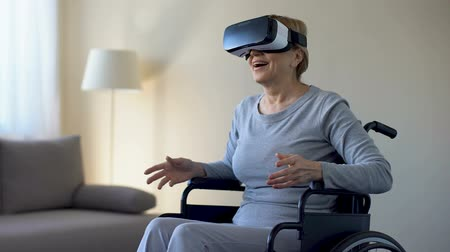 sedmdesátá léta : Impressed grandmother in wheelchair wearing goggles, playing VR game, device Dostupné videozáznamy