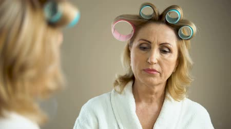 домохозяйка : Aged sad woman with hair curlers and make-up looking at mirror reflection Стоковые видеозаписи