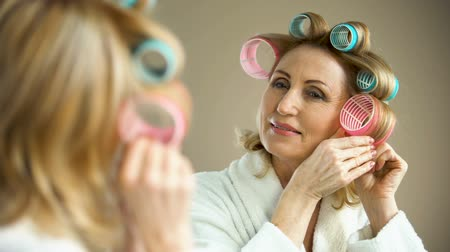 rulli : Beautiful aged lady putting hair curler and smiling into mirror, beauty tricks