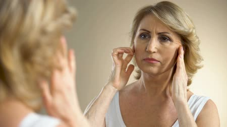 zmarszczki : Unhappy aged woman looking in mirror at home, touching her face, aging process