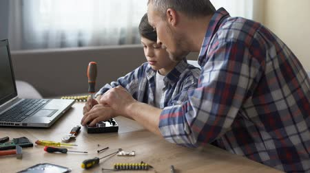 インナー : Caring father teaching his little son to repair hard disk drive at home, hobby
