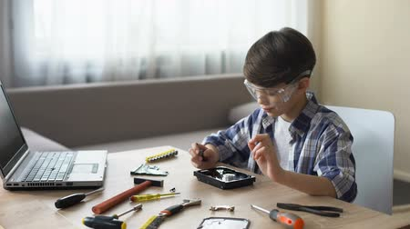 hdd : Boy in glasses working on school project, attentively untwisting PC detail Stock Footage