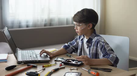 harde schijf : Curious boy in safety glasses searching for HDD instructions on laptop, hobby Stockvideo
