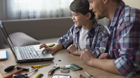 servizi informatici : Son and father sitting at table, searching PC video tutorial on laptop together