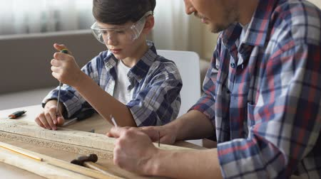 schroevendraaier : Cute attentive boy working with screwdriver and wood, father teaching son