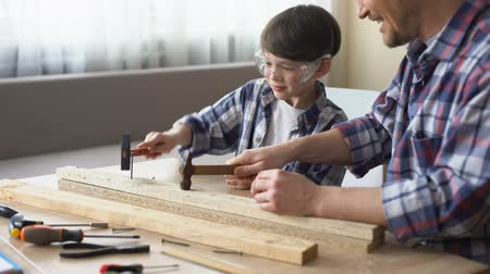 trabalhador manual : Joyful father and son hammering nail in wooden plank, family leisure, support