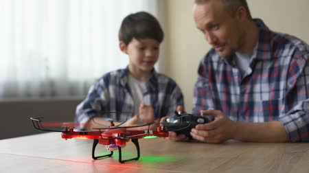 telefonkagyló : Funny father helping son to use remote control of quadrocopter, technologies