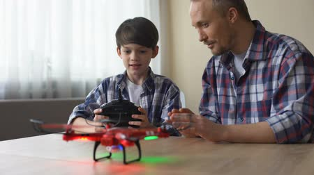 começando : Excited little boy operating new drone model at home, father helping his son