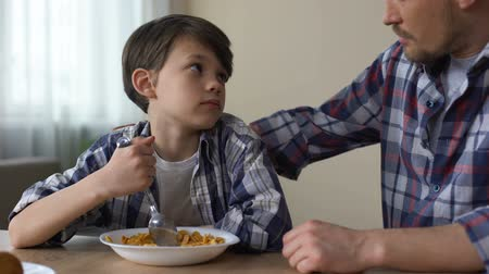 smutek : Little sad boy mixing cornflakes with spoon, looking at father, poor appetite Wideo