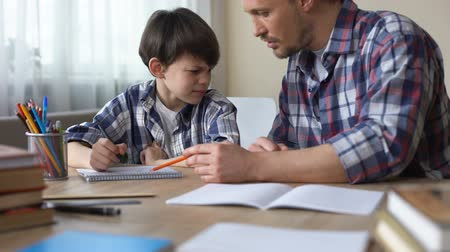 disobedient : Dad sitting at the table and making his capricious son to do homework, education Stock Footage
