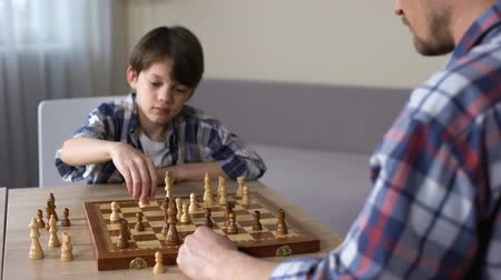 pieza de ajedrez : Father playing chess with little son at home, leisure activity, childhood hobby Archivo de Video