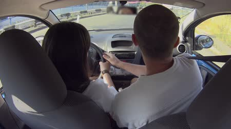 geçti : Woman student in car turning right with help of driving instructor, education Stok Video