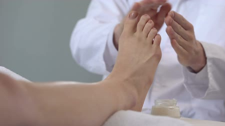 nogi : Specialist doing feet massage using cream, cosmetology procedures, beauty salon