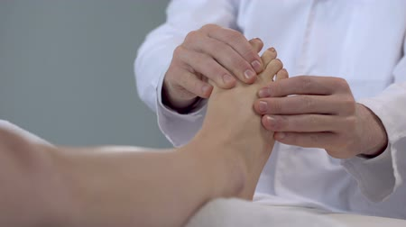 kotník : Doctor massaging patient feet, rehabilitation procedures after leg fracture