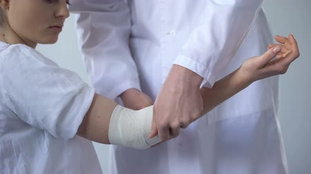 covering : Doctor bandaging injured patient hand, first aid for sprain in trauma clinic