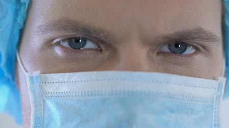 preventive : Competent handsome male physician with blue eyes looking at camera, closeup Stock Footage