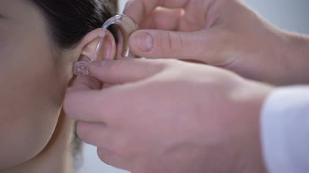 adattare : Closeup of ear with hearing aid, young deaf woman adjusting to environment Filmati Stock