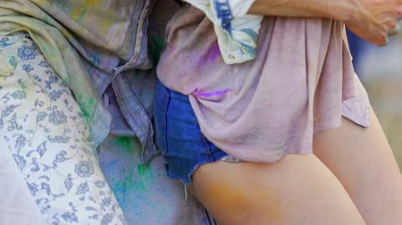 pintado : Playful girl flirting with man, dancing in colorful powder at Holi festival