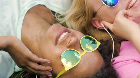 playlist : Happy female friends in earphones listening to music together, lying on grass Stock Footage