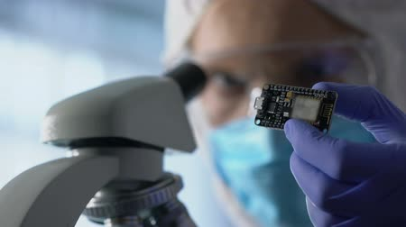 nanotechnologia : Technician examining chip, using microscope to run diagnosis and upgrade device Wideo