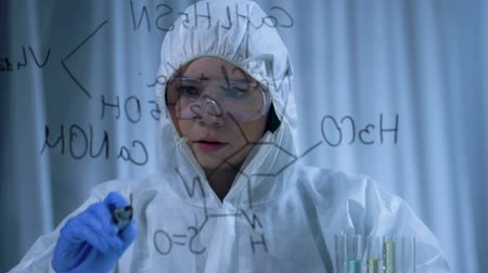 inventing : Attractive female chemist writing complex chemical formula on transparent board Stock Footage