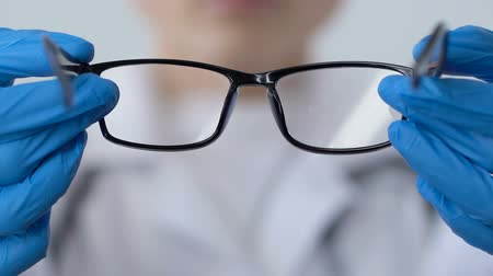 optyk : Optometrist offering eyeglasses patient, eyesight checkup, doctor prescription