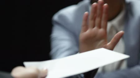 venality : Woman showing stop gesture while man offering white envelope, bribe reject Stock Footage