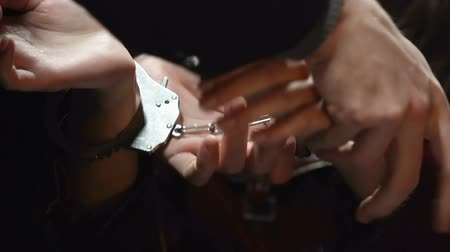 kajdanki : Police officer handcuffing female impudent lawbreaker in room.